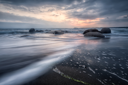Amazing sea sunrise with slow shutter and waves flowing out Archivio Fotografico - 118435761