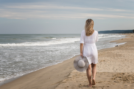 Rear view of a beautiful young woman in white dress and summer hat walking on the sandy beach Archivio Fotografico - 118435731