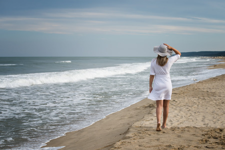 Rear view of a beautiful young woman in white dress and summer hat walking on the sandy beach
