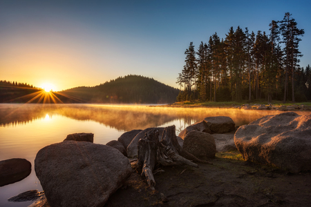 Beautiful sunrise view with sun rays over a mountain lake surrounded by conifers. Shiroka Polyana dam in Rhodopi Mountains, Bulgaria. Archivio Fotografico - 118435733