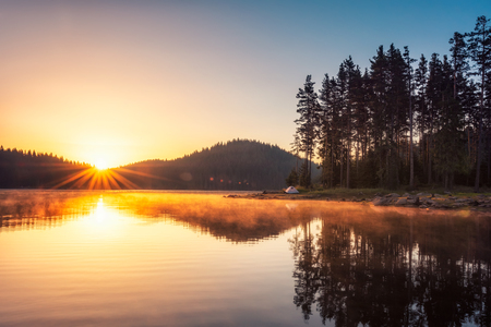 Beautiful sunrise view with sun rays over a mountain lake surrounded by conifers. Shiroka Polyana dam in Rhodopi Mountains, Bulgaria.