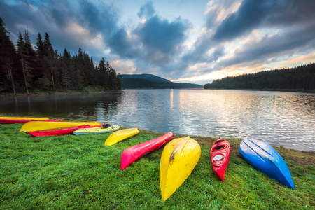 Beautiful summer morning view of Beglik dam in Rhodopi Mountains, Bulgaria with colorful canoes scattered on the grass to dry