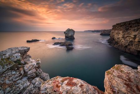 Magnificent sea sunrise at the rocky Black sea coast with a lone rock in the sea