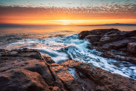 Stormy sea with colorful sunrise sky at the rocky coastline of the Black Sea Фото со стока - 118435746