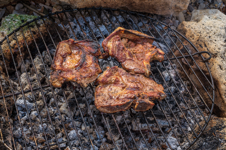 Seasoned pork steaks cooking on the charcoal bbq grill Archivio Fotografico - 126045641