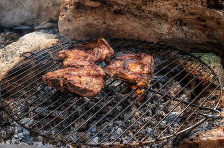 Seasoned pork steaks cooking on the charcoal bbq grill Archivio Fotografico - 126045638