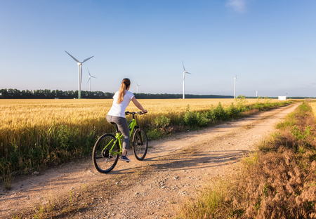 Woman rides a bicycle on a field  path 写真素材 - 126045642