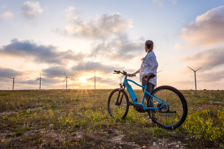 A woman with a bike enjoys the view of sunset over a summer field with a wind farm