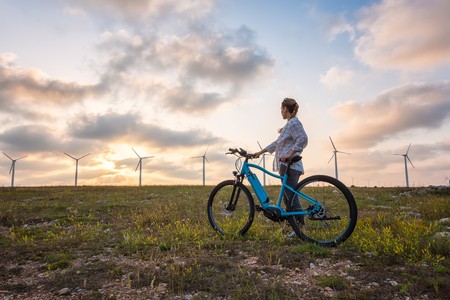 A woman with a bike enjoys the view of sunset over a summer field with a wind farm Archivio Fotografico - 126045620