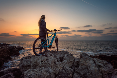Rear view of a woman with a bike enjoys the view of sunrise at the rocky Black Sea coast