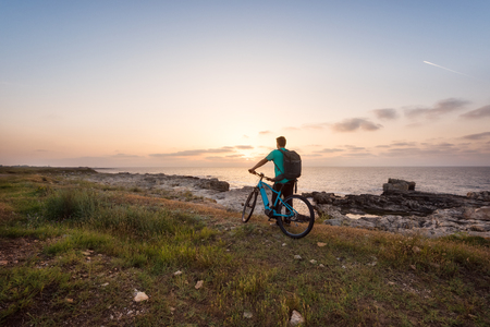 Rear view of a man with a backpack and a bike enjoys the view of sunrise at the Black Sea coast Archivio Fotografico - 126045623