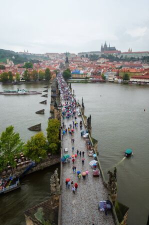 PRAGUE, CZECH REPUBLIC - SEPTEMBER 20, 2014: A rainy view over Charles Bridge in Prague, filled with colorful umbrellas