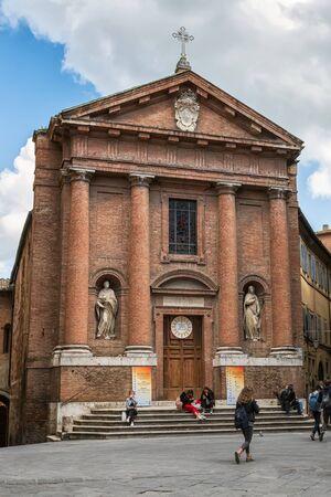 SIENA, ITALY - APRIL 9, 2019: Tourists are walking around San Cristoforo church in Siena, Italy