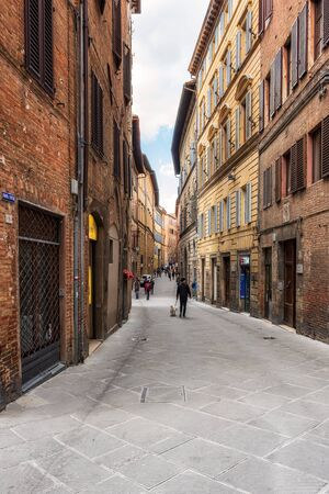 SIENA, ITALY - APRIL 9, 2019: Tourists are walking trough the narrow medieval streets in Siena, Italy