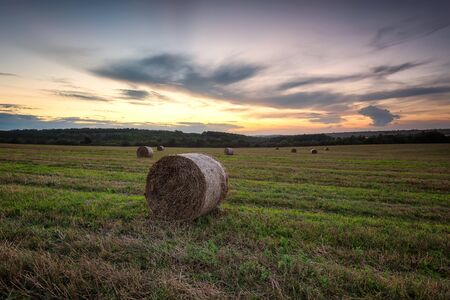 Magnificent sunset view with a field full of hay bales