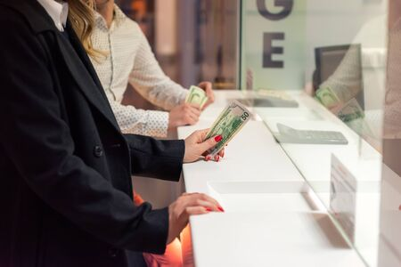 Female hand with money at cash desk. Currency exchange concept.