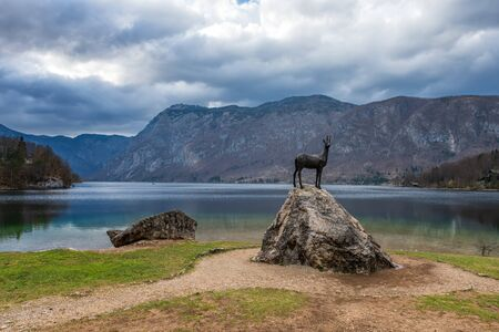 Panoramic spring view of Bohinj lake with the Statue of Golden horn, located within the Bohinj Valley of the Julian Alps, Slovenia.