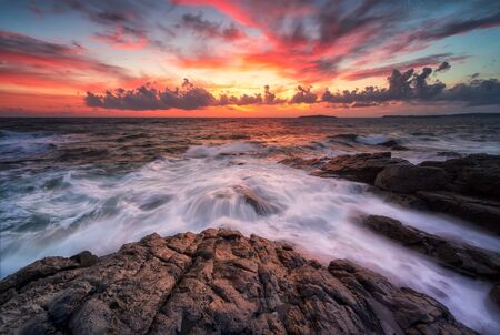 Stormy sea with colorful sunrise sky at the rocky coastline of the Black Sea 写真素材