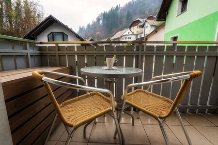 Chairs and round table on a balcony with a scenic view of mountain village Bled, Slovenia