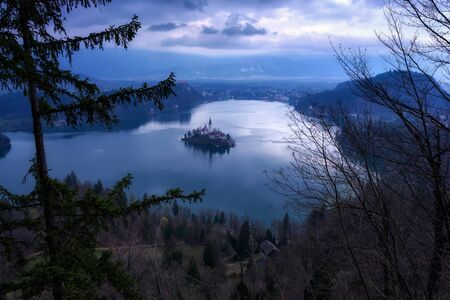 Panoramic view of Bled lake with St. Marys Church of the Assumption on the small island and mountains in the background in blue hour before sunrise