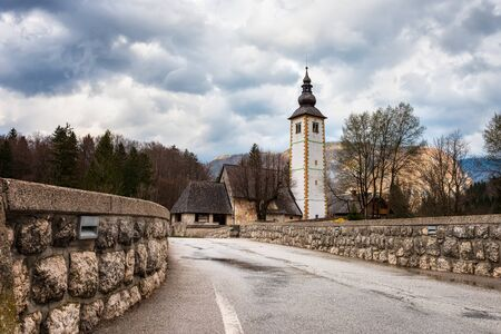Amazing spring view of Bohinj lake with the church of St John the Baptist and the stone bridge in Triglav National Park, located in Julian Alps, Slovenia.