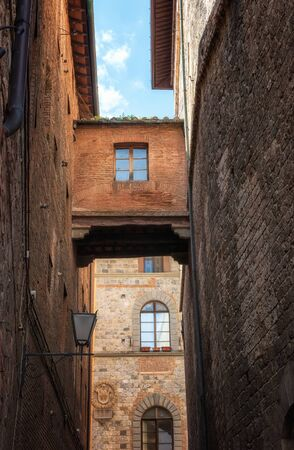 Tuscany Siena medieval town, narrow streets and an enclosed walkway serving as a connection or bridge between two buildings