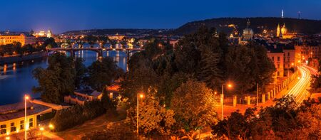 Aerial panoramic night view of famous bridges in Old Town of Prague over Vltava river and streets of Mala Strana