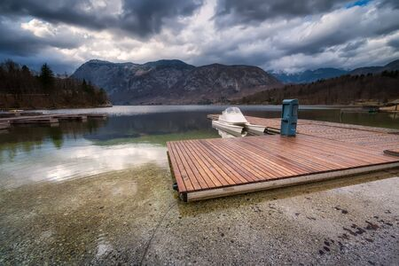 Panoramic view with wooden pier and motor boat at Bohinj lake, located within the Bohinj Valley of the Julian Alps, Slovenia.