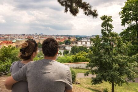 A couple enjoys the view of famous bridges in Old Town of Prague in Czech Republic over Vltava river 写真素材