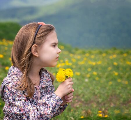 Lovely little girl playing in the spring field full of dandelions