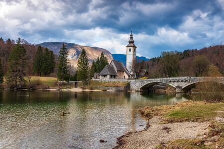 Panoramic spring view of Bohinj lake with the church of St John the Baptist and the stone bridge in Triglav National Park, located in Julian Alps, Slovenia. 写真素材