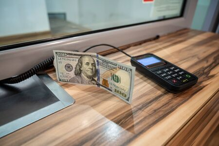 One hundred dollars banknote and terminal device at cash desk. Currency exchange concept.