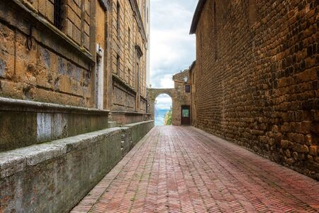 Amazing view with a narrow medieval street with arch gate in old town of Pienza in Tuscany, Italy