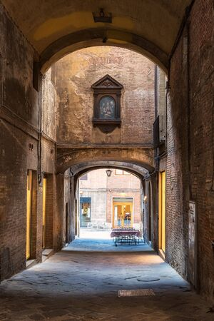 Romantic view with Siena medieval narrow streets with high brick walls, arch, iconostasis and an empty restaurant table