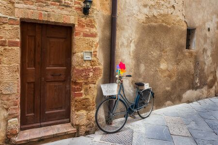 Amazing view with a bike on a stone wall at narrow medieval street of old town of Pienza in Tuscany, Italy