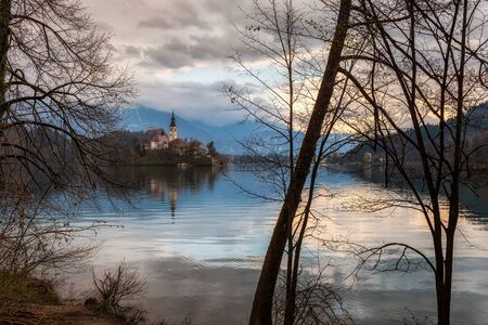 Amazing colorful view of Bled lake with St. Marys Church of the Assumption on the small island and mountains in the background at sunset
