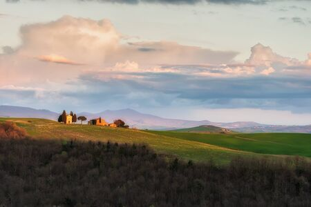 Amazing spring landscape with green rolling hills and well known Vitaleta chapel near Pienza in the heart of Tuscany in golden hour before sunset