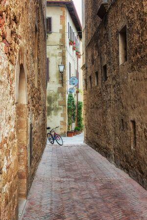 Amazing view with a bike on a stone wall at narrow picturesque medieval street of old town of Pienza in Tuscany, Italy