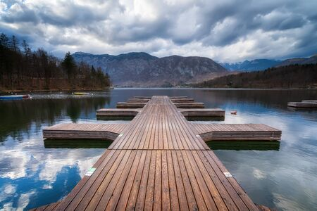 Panoramic view with wooden pier at Bohinj lake, located within the Bohinj Valley of the Julian Alps, Slovenia.