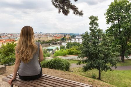 A girl enjoys the view of famous bridges in Old Town of Prague in Czech Republic over Vltava river 写真素材
