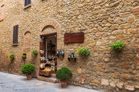 Pienza, Italy - April 10, 2019: Amazing view with narrow picturesque medieval street and a small shop with local food and wine. Banco de Imagens