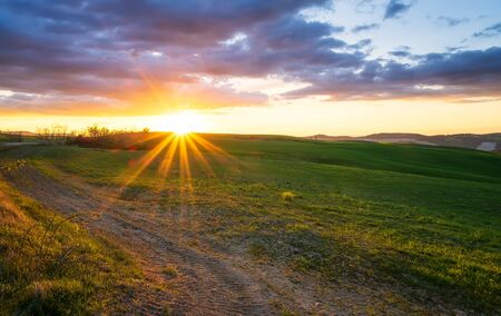 Amazing spring landscape with suns rays touching the endless green rolling hills of Tuscany at sunset