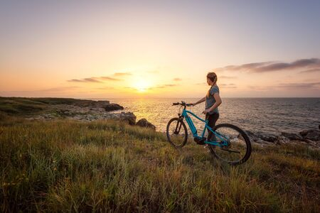 Morning view of a woman with a bike enjoys the view of sunrise at the rocky Black Sea coast 写真素材