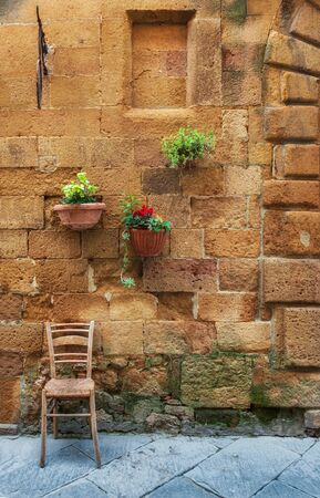 Flower decoration on a stone wall in the old provincial Tuscany town Pienza, Italy.