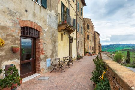 A narrow picturesque medieval street along the city wall and view to the valley in old town of Pienza in Tuscany, Italy