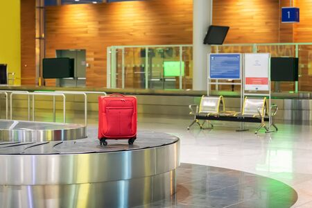 Red suitcase on luggage conveyor belt in an arrivals lounge of airport terminal. Selective focus. 写真素材