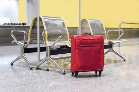 Red suitcase in an arrivals lounge of airport terminal. Selective focus.