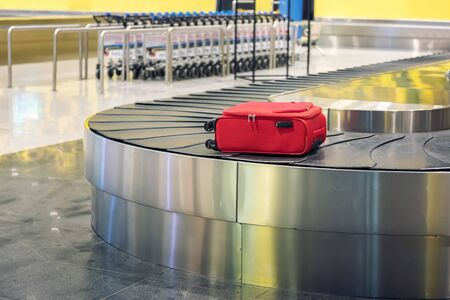 Suitcase on luggage conveyor belt in an arrivals lounge of airport terminal. Selective focus. 写真素材