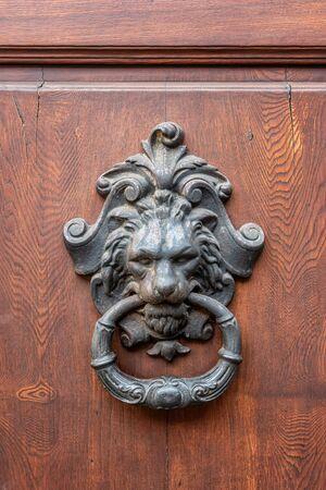 Old metal door handle in the form of a lion. Door knocker closeup background, Florence, Italy
