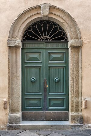 An old decorated vintage door in historical centre of Florence, Italy 写真素材
